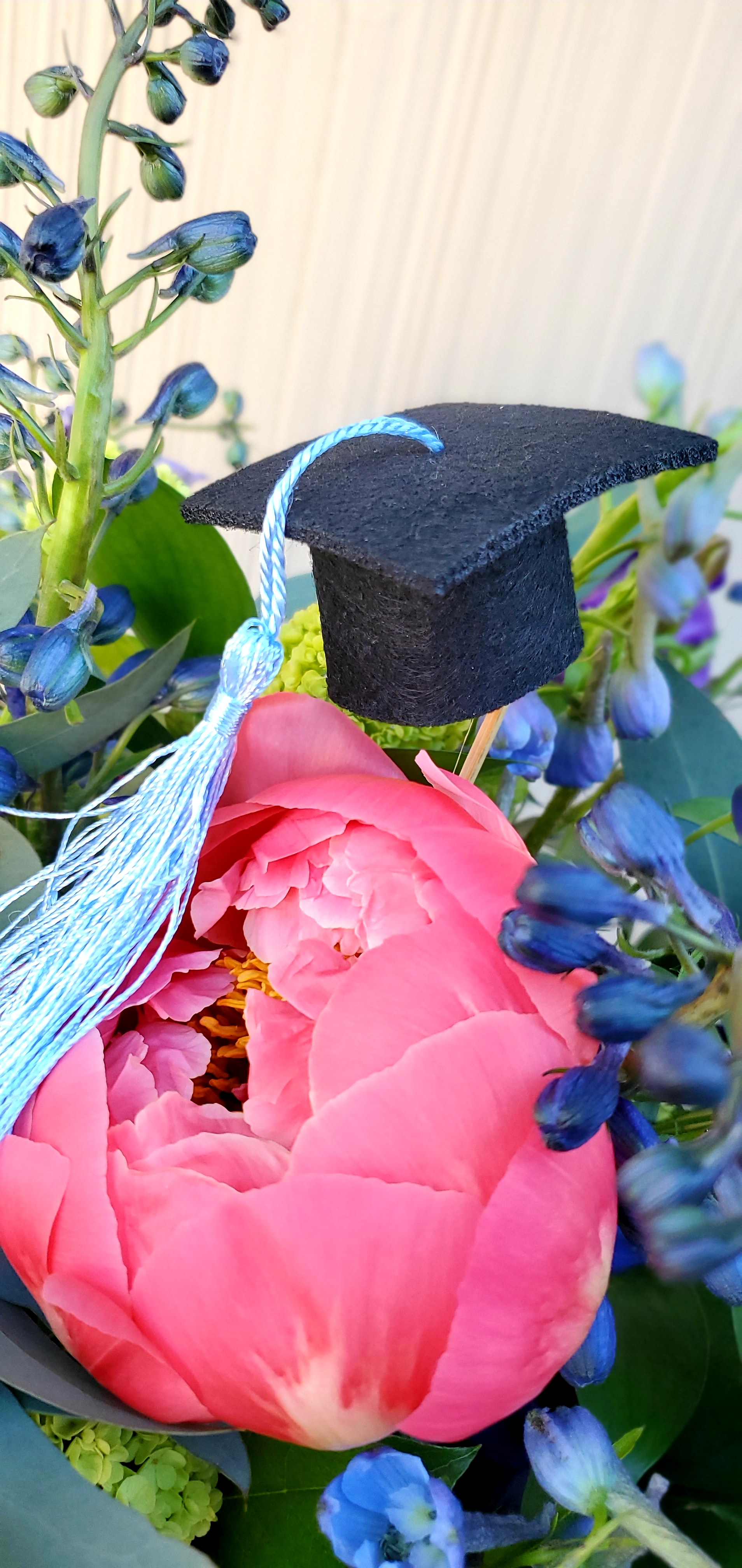Flower bouquet with tiny grad cap in middle