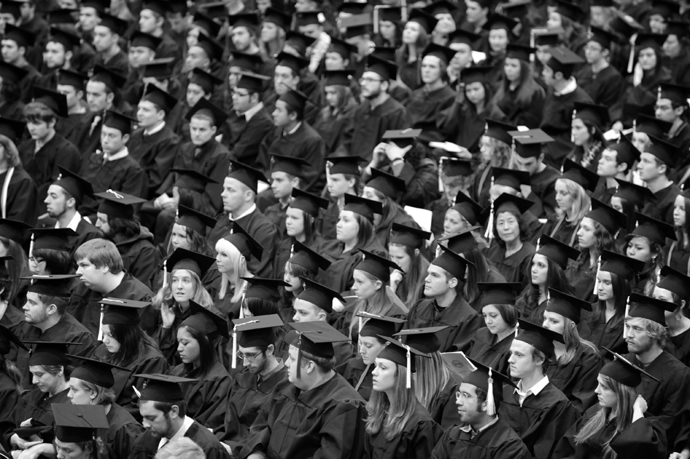 black and white photo of crowd with graduates all in cap and gowns.